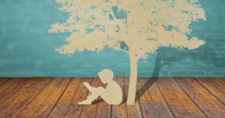 Boy reading by tree